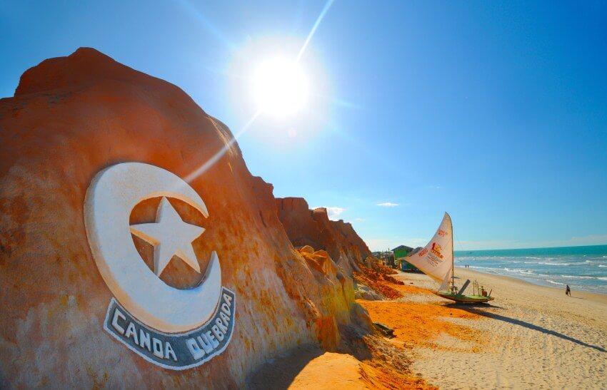 spiaggia e roccia rossa con simbolo di canoa quebrada