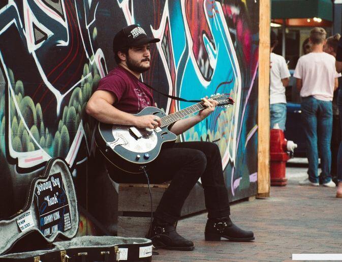 ragazzo busker suona per strada