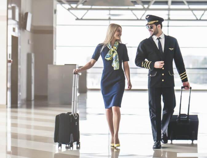 due assistenti di volo passano attraverso l'aeroporto